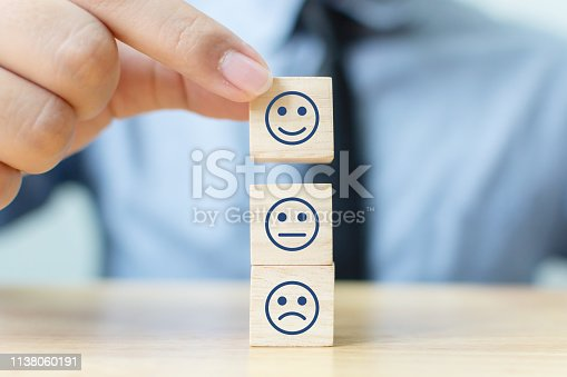 693589426 istock photo Hand of a businessman chooses a smiley face on wood block cube, The best excellent business services rating customer experience, Satisfaction survey concept 1138060191