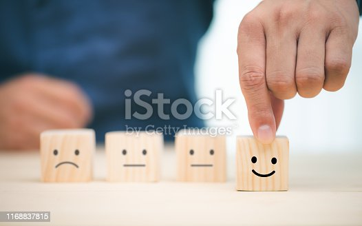 Hand of a businessman chooses a smiley face on wood block cube, The best excellent business services rating customer experience, Satisfaction survey concept