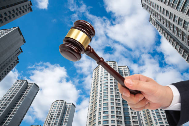 Hand of a businessman holding a judge gavel on the building background. Auction or bankruptcy concept. stock photo