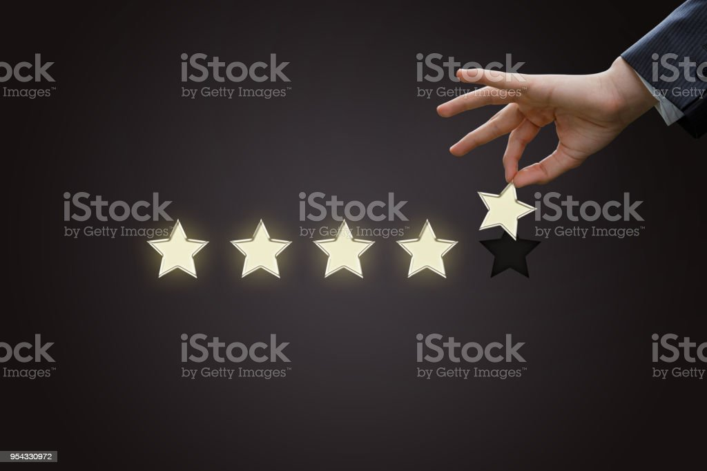 Hand of a businessman holding the fifth star. stock photo
