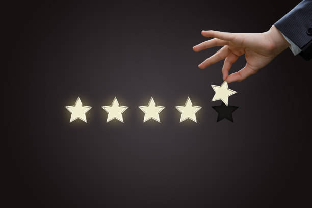 Hand of a businessman holding the fifth star. Hand of a businessman holding the fifth star on a dark background. loyalty stock pictures, royalty-free photos & images