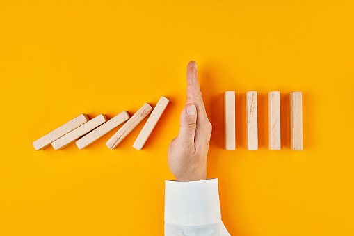 Hand of a businessman stopping domino effect on yellow background. Concept of risk protection, business solution or successful intervention strategy.
