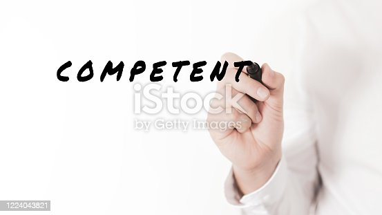 Hand of a businessman writing a word Competent with black marker in a conceptual image of competency and merit
