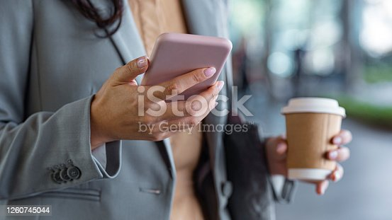 Connected on the go: a happy Asian businesswoman texting on her mobile phone on the street while drinking takeaway coffee.