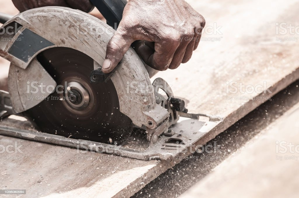 Hand of a carpenter using a circular saw to cut a wooden plank. Tool...