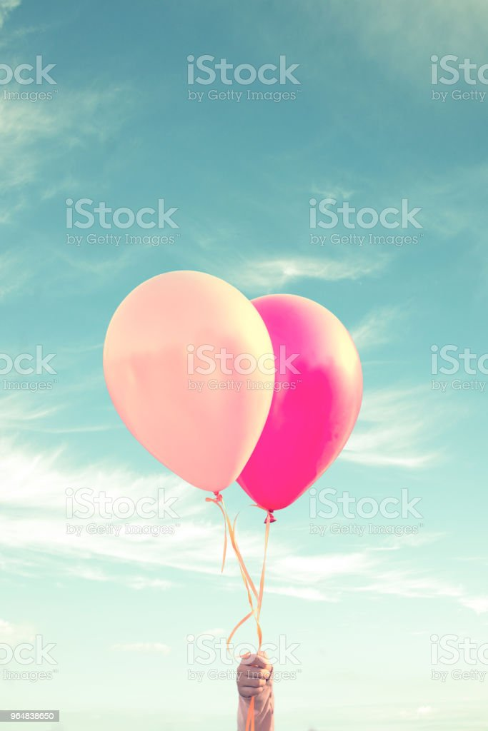Hand of a child holding balloons, sky background, vintage process royalty-free stock photo