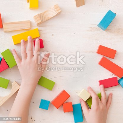 657779378 istock photo hand of a child playing with colorful wooden toy blocks and building shapes. 1057491444