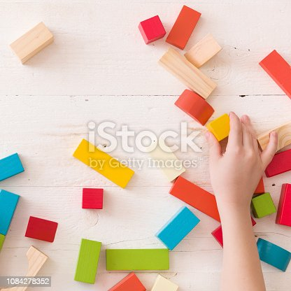 657779378 istock photo hand of a child playing with colorful wooden toy blocks and building shapes. 1084278352