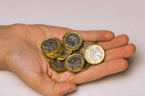hand of a child with British pound coins stock photo