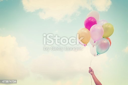 istock A hand of a girl holding multi-colored balloons 473874734