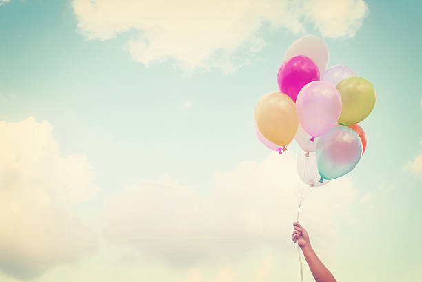 A hand of a girl holding multi-colored balloons stock photo
