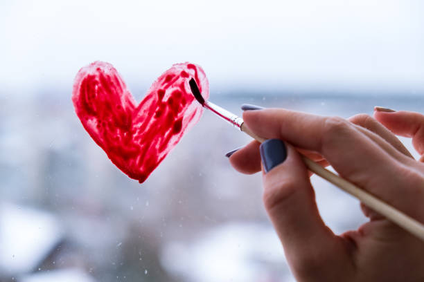Hand of a girl with a paintbrush painting red heart on a window, stay home, quarantine leisure, let's all be well, Valentines day, Love stock photo