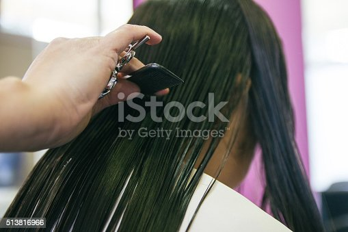 istock Hand of a hairdresser with scissors combing hair 513816966