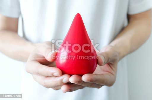Hand of a healthy man hold symbol blood.Help and Health Concepts