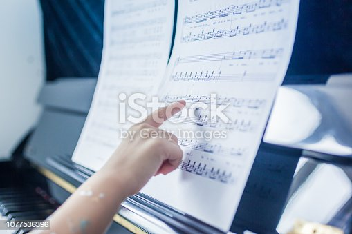 Close-up hand of a kid pointing at sheet music and playing piano.