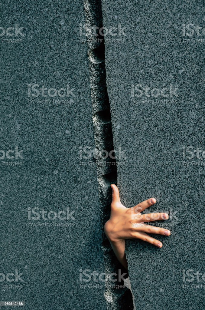 Hand of a Kid Through Narrow Gap in Marble Wall stock photo