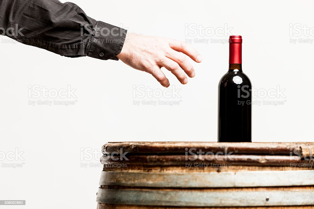 hand of a man about to grasp a wine bottle stock photo