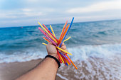 Hand of a man holding a colorful disposable straw on the beach