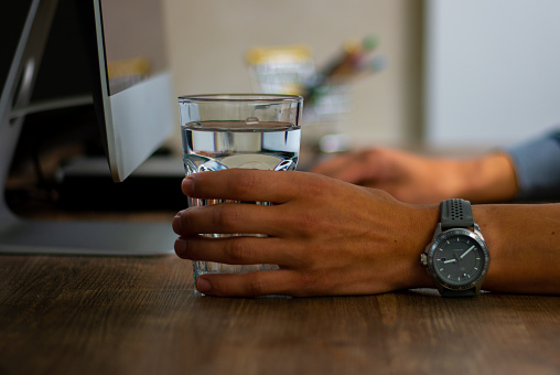 509867718 istock photo Hand of a man holding a glass of water 1178914095