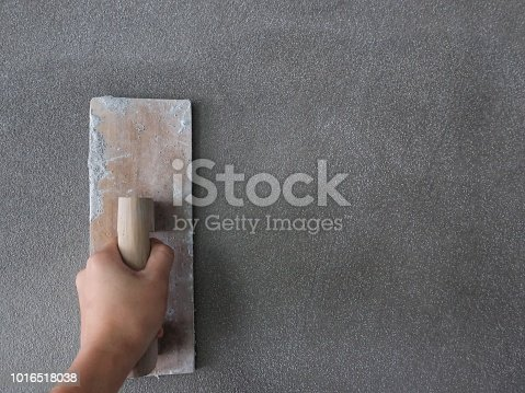 Hand of a man holds a trowel for plastering a cement wall or skimming coating on plaster walls