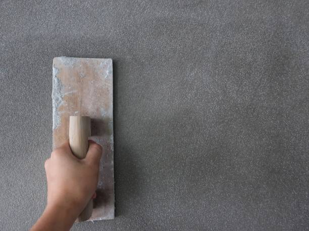 Hand of a man holds a trowel for plastering a cement wall
