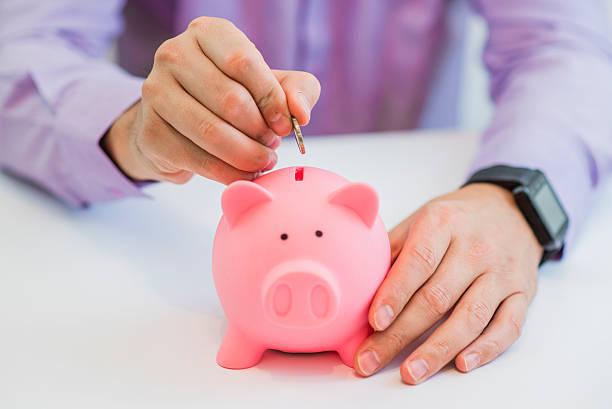 hand of a man placing a coin into piggy bank - gerente de cuentas fotografías e imágenes de stock