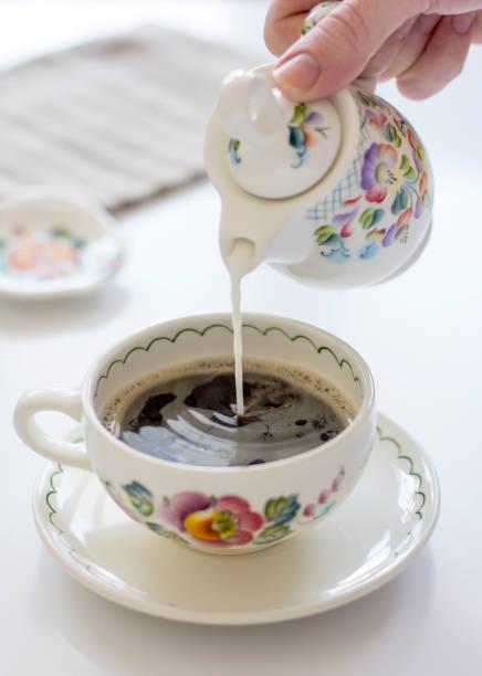 hand ein mann gießen milch in schwarzen kaffee - porzellan druck stock-fotos und bilder