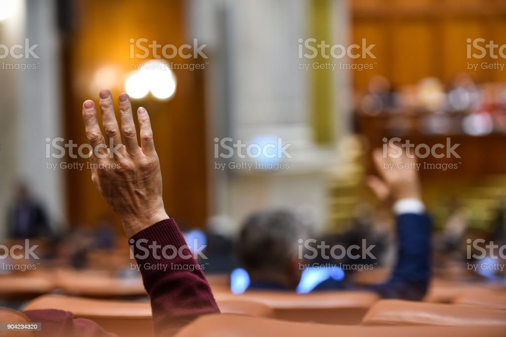 Hand of a man raised in the air during a voting procedure stock photo