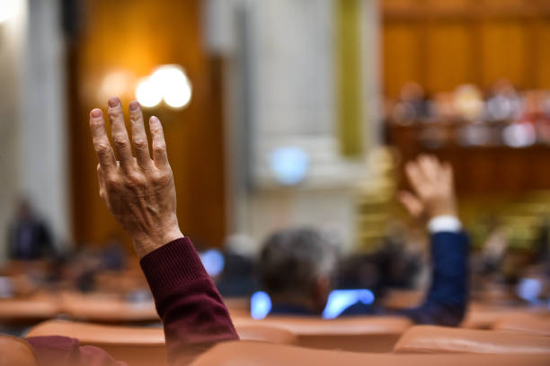 hand of a man raised in the air during a voting procedure - citizenship stock photos and pictures
