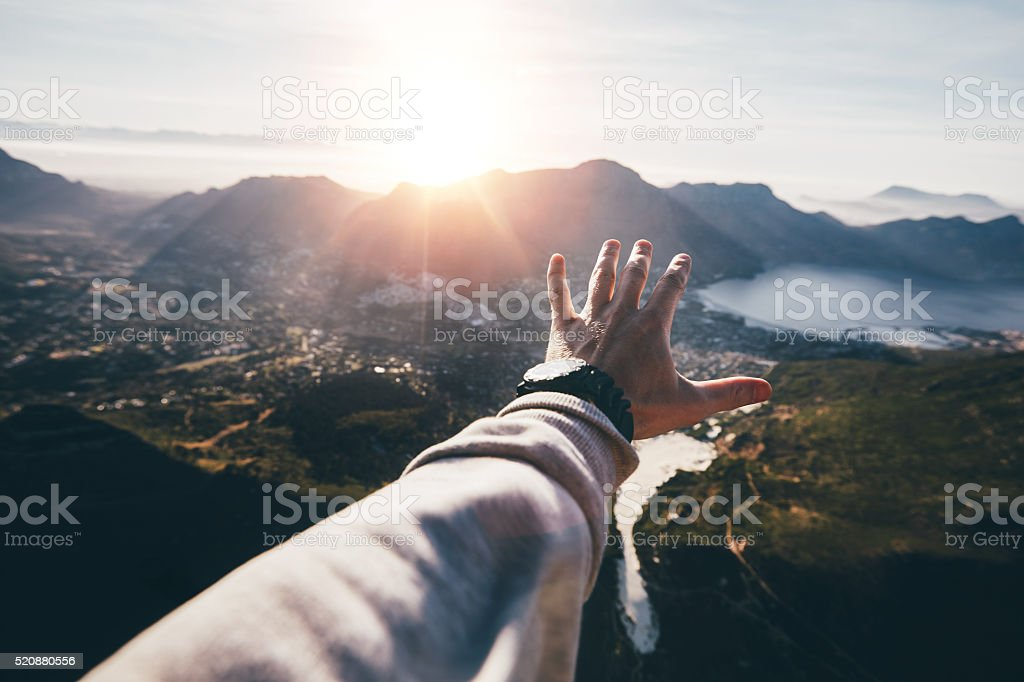 Hand of a man reaching out the beautiful landscape stock photo