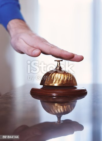 840883328 istock photo Hand of a man using hotel bell 591844144