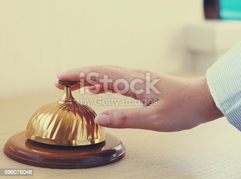 840883328 istock photo Hand of a man using hotel bell 596076048