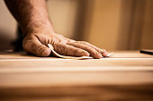 istock Hand of a Mature Carpenter Rubbing Wood With Sand Paper 1286190806