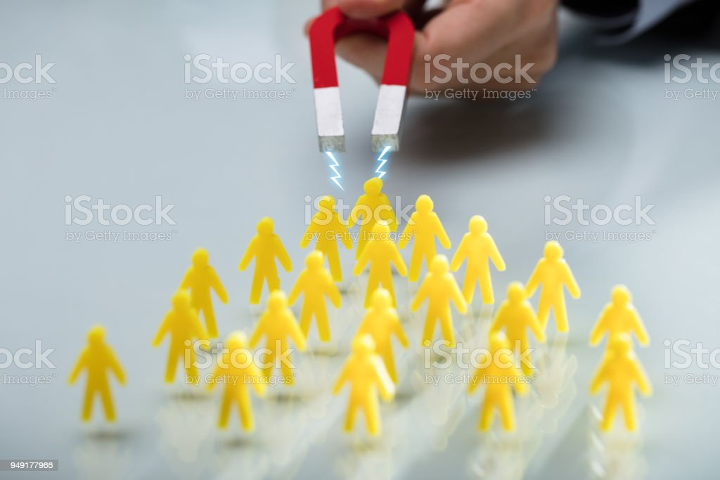 Hand Of A Person Attracting Group Of Figurines With Magnet stock photo