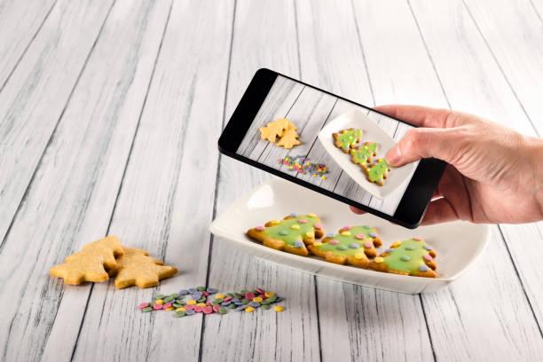 hand einer person, die fotos mit einem handy zu einigen köstlichen weihnachtsbäumen aus lebkuchen-cookies mit grünem frost und farbigem zuckerkonfetti verziert. weihnachtsdesserts - weihnachtsbilder zum ausmalen stock-fotos und bilder