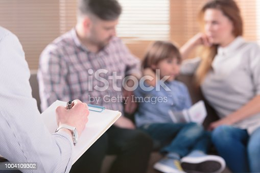 istock Hand of a professional family psychotherapist writing notes in front of a couple with a child in a blurred background during a consultation 1004109302