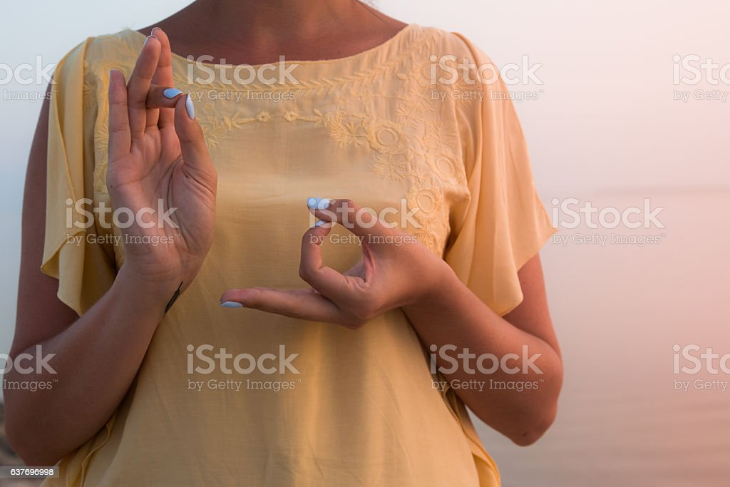 hand of a woman meditating in a yoga pose stock photo