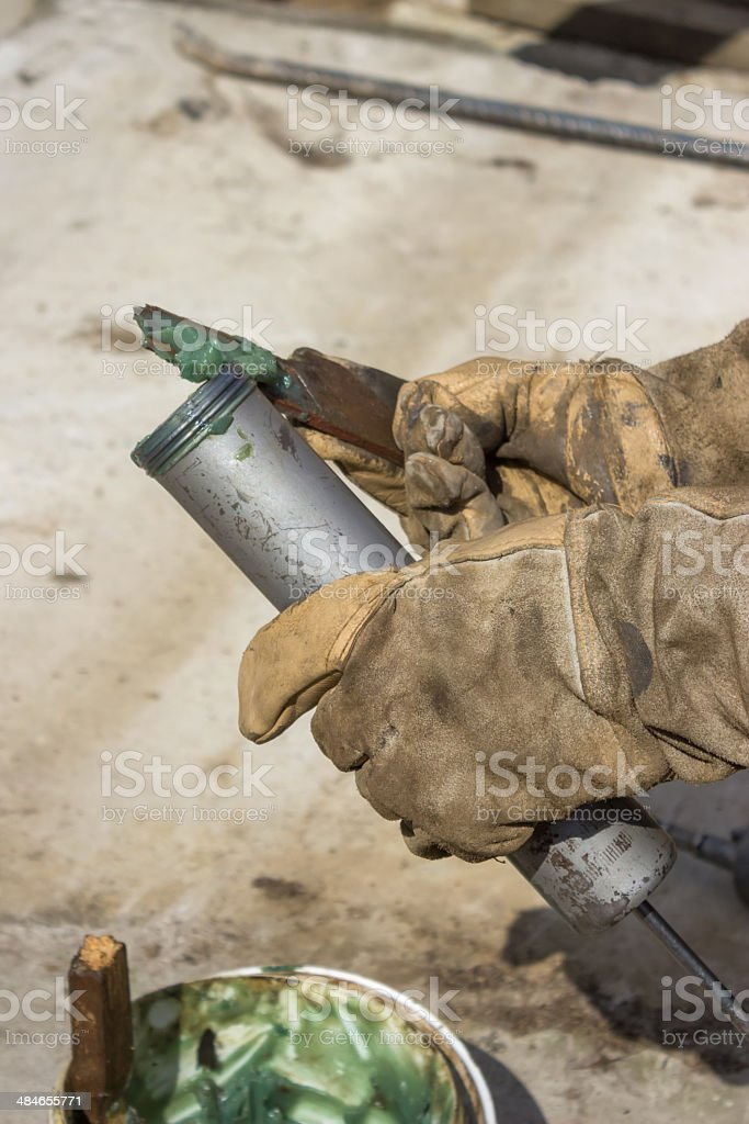 hand of a workman filling grease gun 2 stock photo
