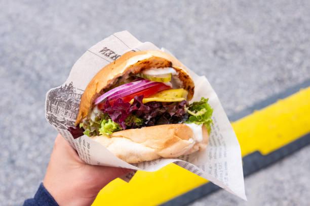 Main d'un jeune homme tenant un burger bio végétalien avec patty de seitan dans sa main lors d'un festival de cuisine de rue - Photo