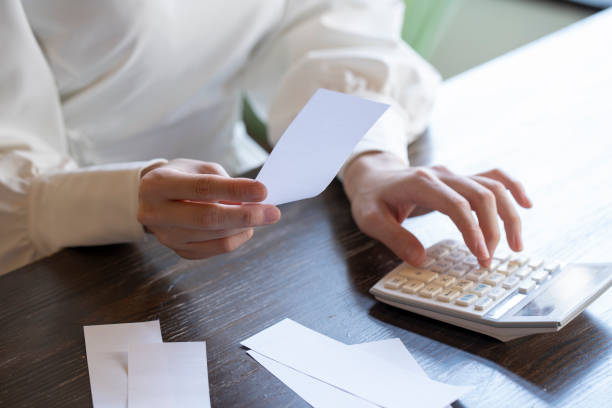 Hand of a young woman who looks at the receipt and does accounting stock photo