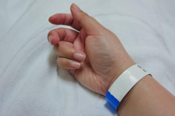 una mano de adulto paciente femenino asiático con pulsera de hospital. - eventos de etiqueta fotografías e imágenes de stock