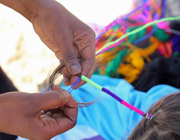 hand der afrikanerin verschränkt die haare von einem kleinen mädchen mit - ghana zöpfe stock-fotos und bilder