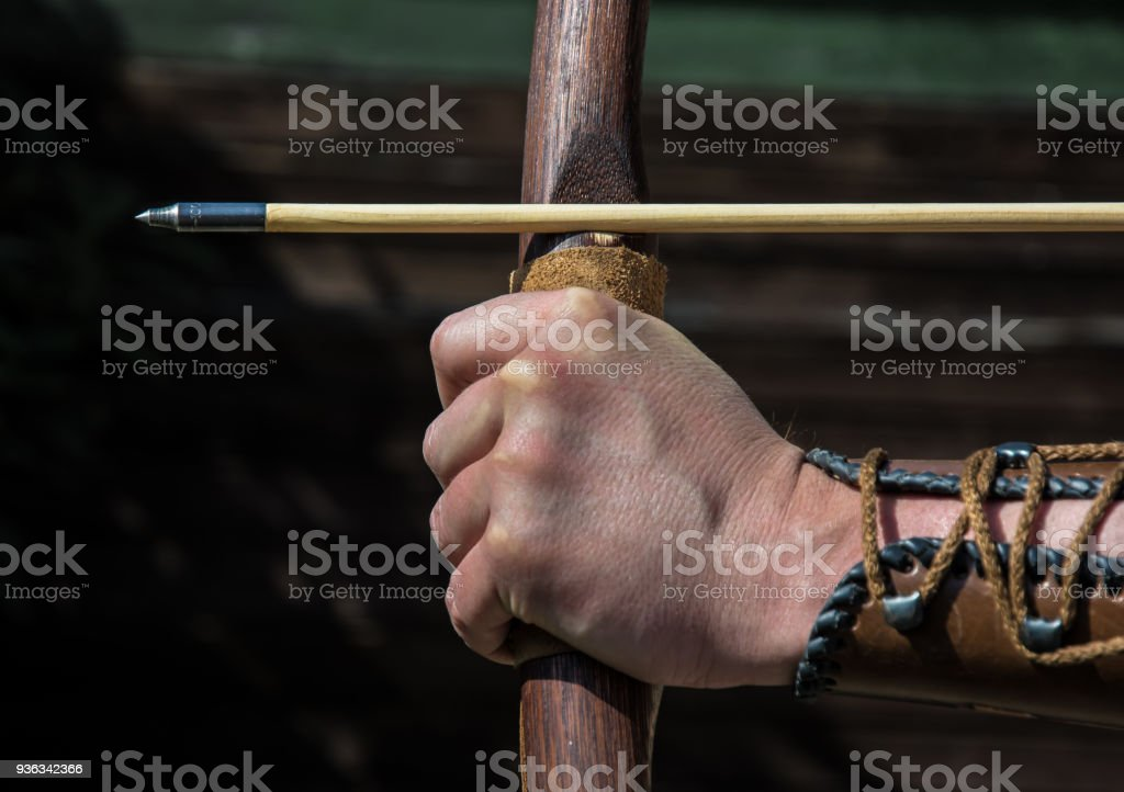 Hand of an archer holds bow and arrow and aims at target stock photo
