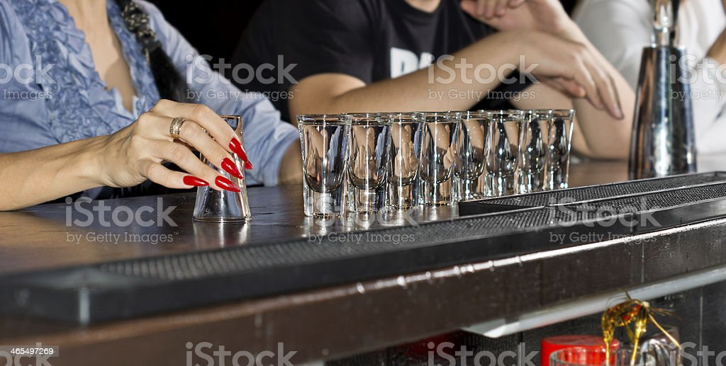 Hand of an elegant woman holding a shot glass stock photo