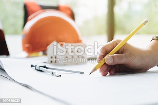 832105172 istock photo Hand of Architect working on blueprint. engineer inspective in workplace and use computer laptop, pencil and home simulator in the design, and foreman using tablet in the job site. 950689032