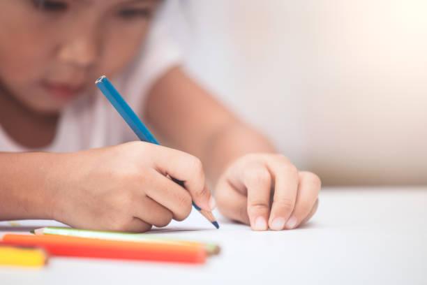 hand des asiatischen kind mädchen zeichnen und malen mit kreide - kreatives schreiben übungen stock-fotos und bilder