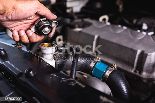 Hand of auto mechanic technician service check cooling water he open radiator cap the in garage