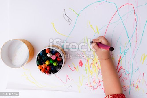 istock A hand of baby drawing lines and shapes with colorful crayons. 810977762
