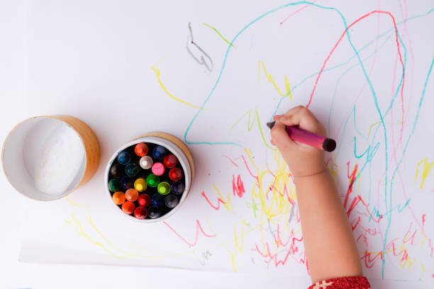 A hand of baby drawing lines and shapes with colorful crayons. stock photo