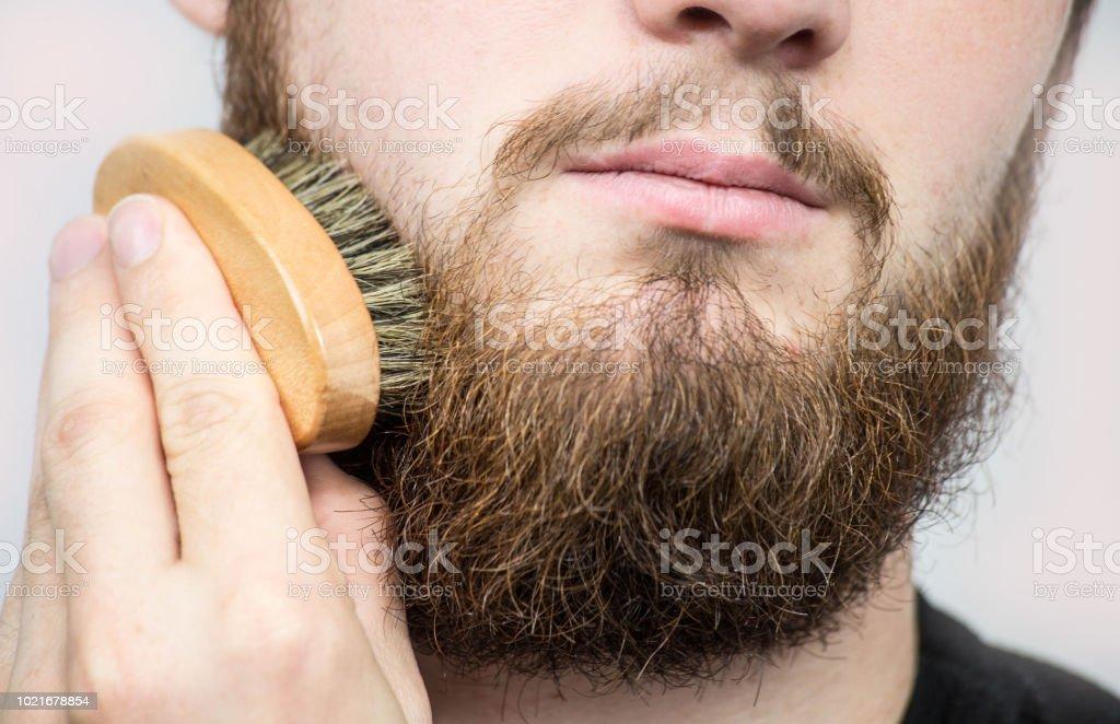 Hand von Friseur Bürsten Bart. Barbershop Kunde, Vorderansicht. Bart Pflege Tipps für Anfänger. – Foto